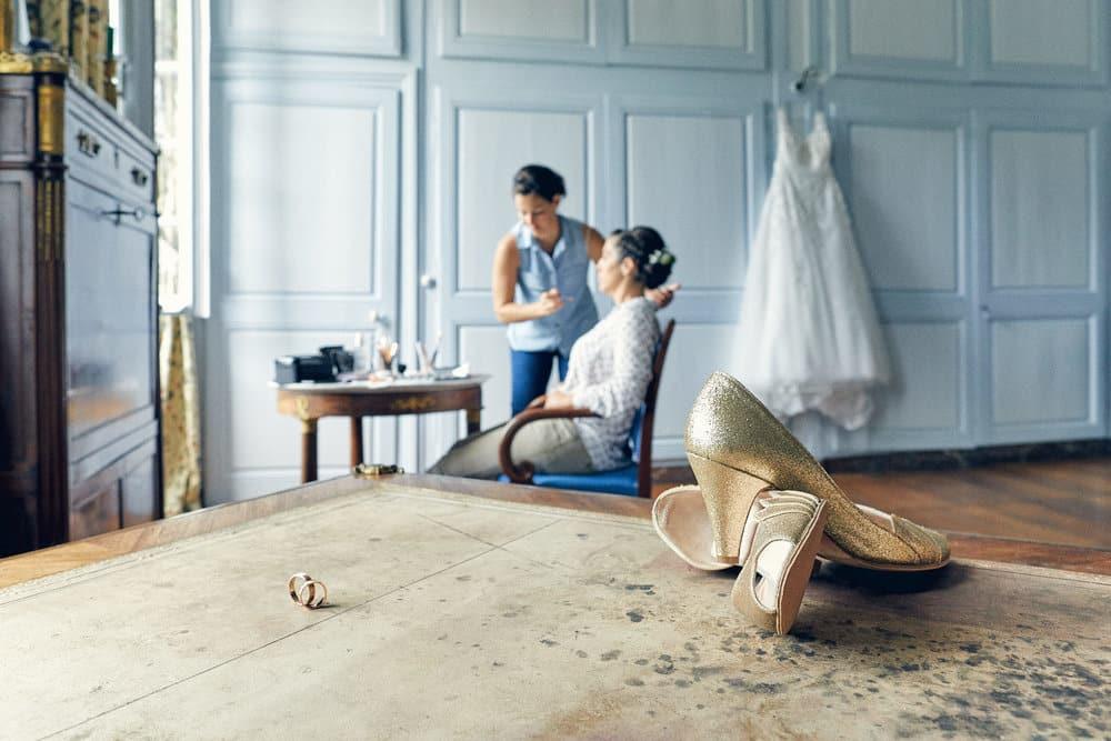 Les préparatifs de la mariée avec la robe de mariage en arrière plan et les chaussures et alliances au premier plan dans la magnifique chambre du Château de Salvanet