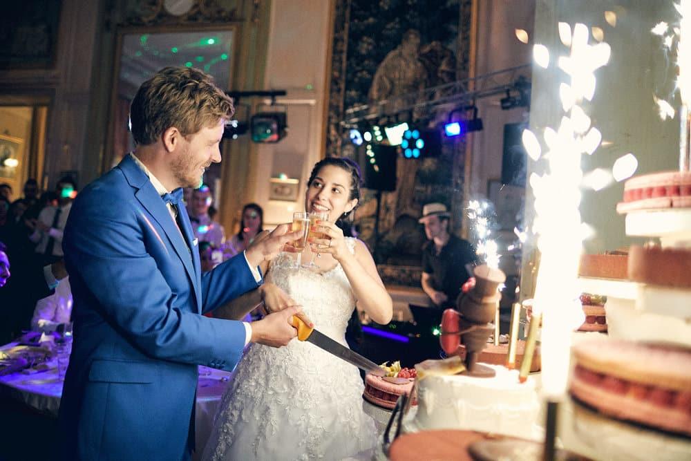Les mariés trinquent à leur mariage devant la pièce montée